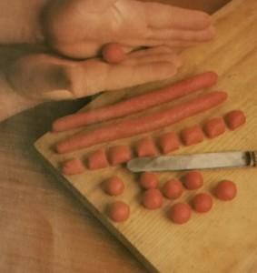 Con le mani arrotolate l'impasto sino ad ottenere dei salsicciotti, che taglierete in quadrati rettangolari per farne successivamente delle palline